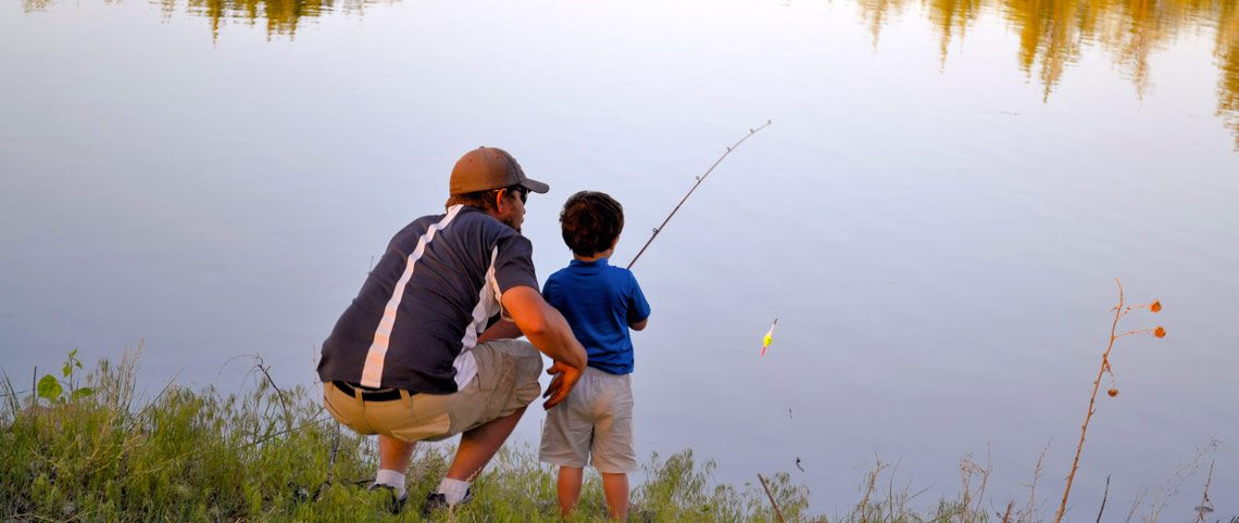 dad and son fishing in lake